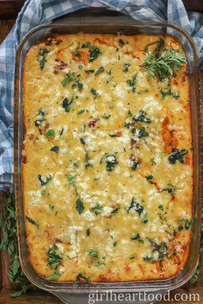 Large pan of vegetarian moussaka garnished with fresh oregano.
