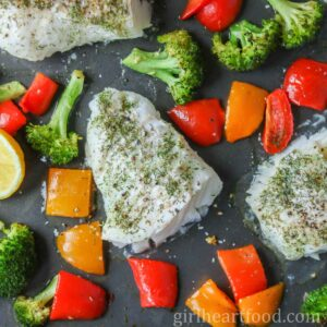 Oven-baked cod fillets with bell pepper and broccoli on a sheet pan.