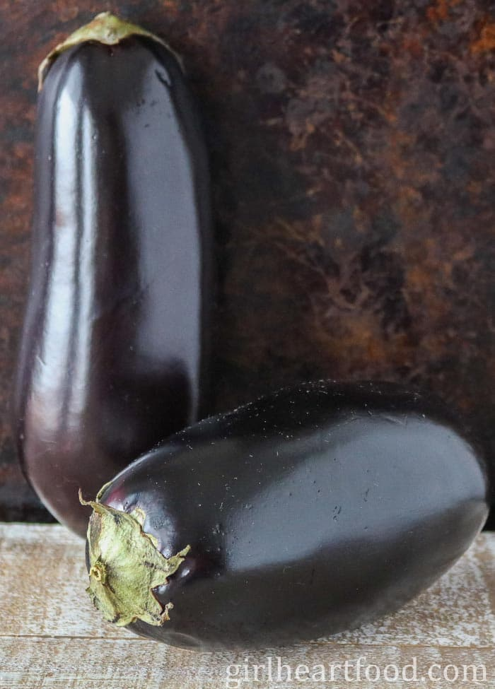 Two uncooked eggplants, one upright and one on its side.