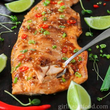 Large, cooked fillet of glazed wild-caught arctic char fish with a fork stuck into the fish, taking some out.