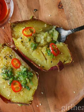 A baked purple sweet potato cut in half and topped with a flavourful butter, chili and sesame seeds.