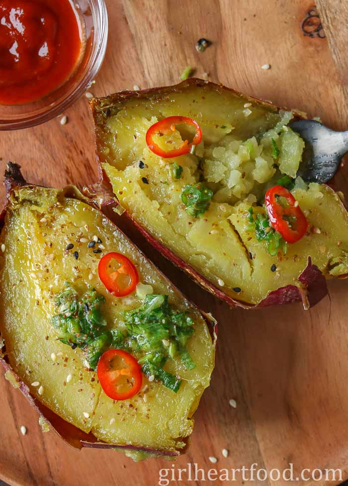 A baked Japanese sweet potato that has been cut in half and garnished with herb butter, sesame seeds and red chili.