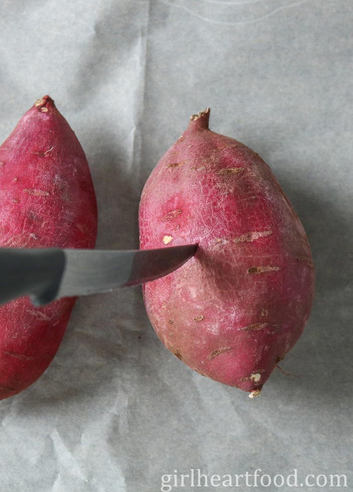 Pricking a Japanese sweet potato with a knife.