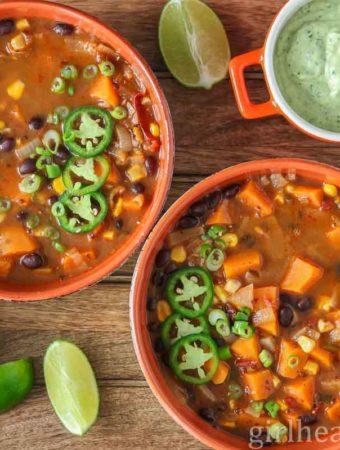 Two bowl of black bean sweet potato soup alongside a dish of avocado creama.