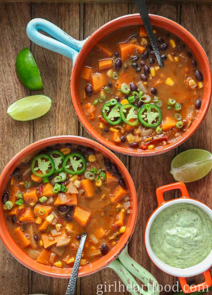 Two bowls of black bean and sweet potato soup garnished with jalapeno and green onion alongside a dish of avocado lime crema.
