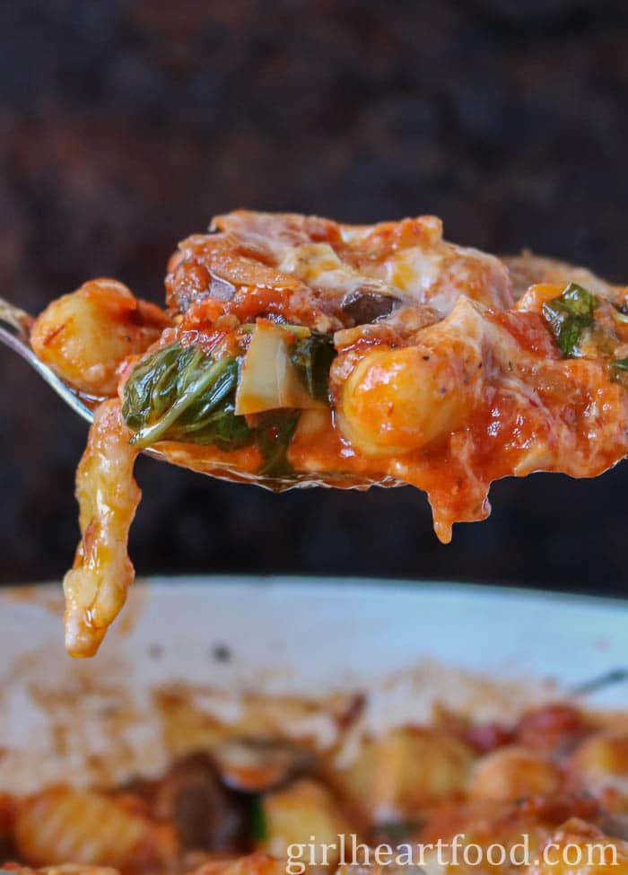 A large spoonful of cheesy baked gnocchi above a skillet of it.