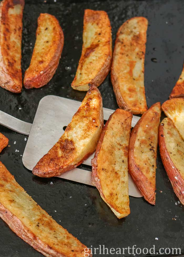 Scooping up homemade potato wedges from a sheet pan with a spatula.