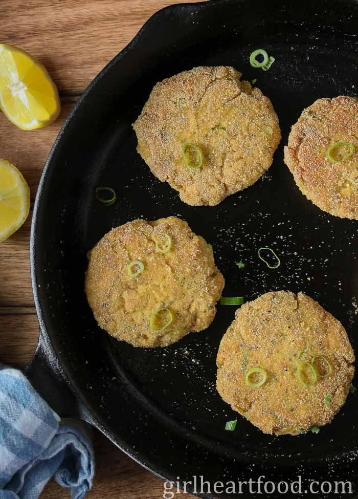 Old-fashioned salmon patties with cornmeal in a cast-iron skillet next to lemon wedges.