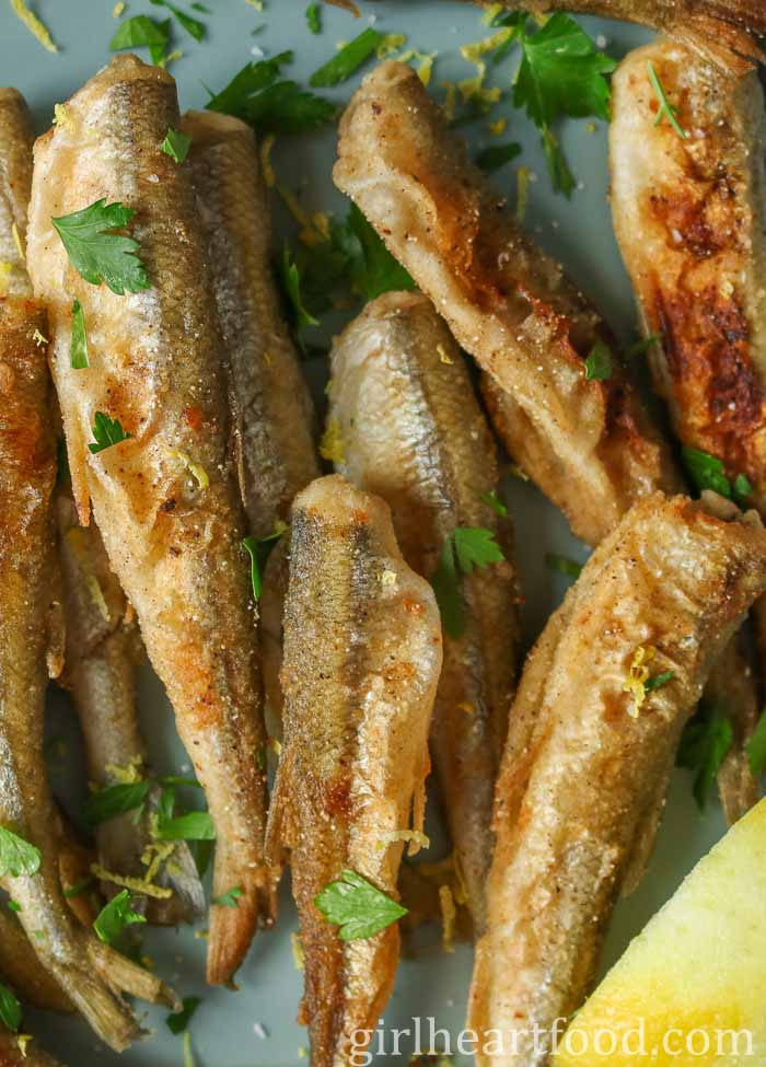 Close up of fried smelt garnished with chopped parsley on a blue plate.