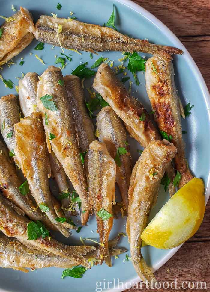 Crispy smelt fish on a blue plate alongside a lemon wedge.