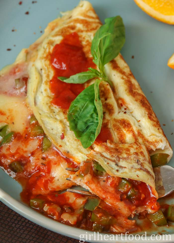 Close-up of a pizza omelette garnished with fresh basil on a blue plate.