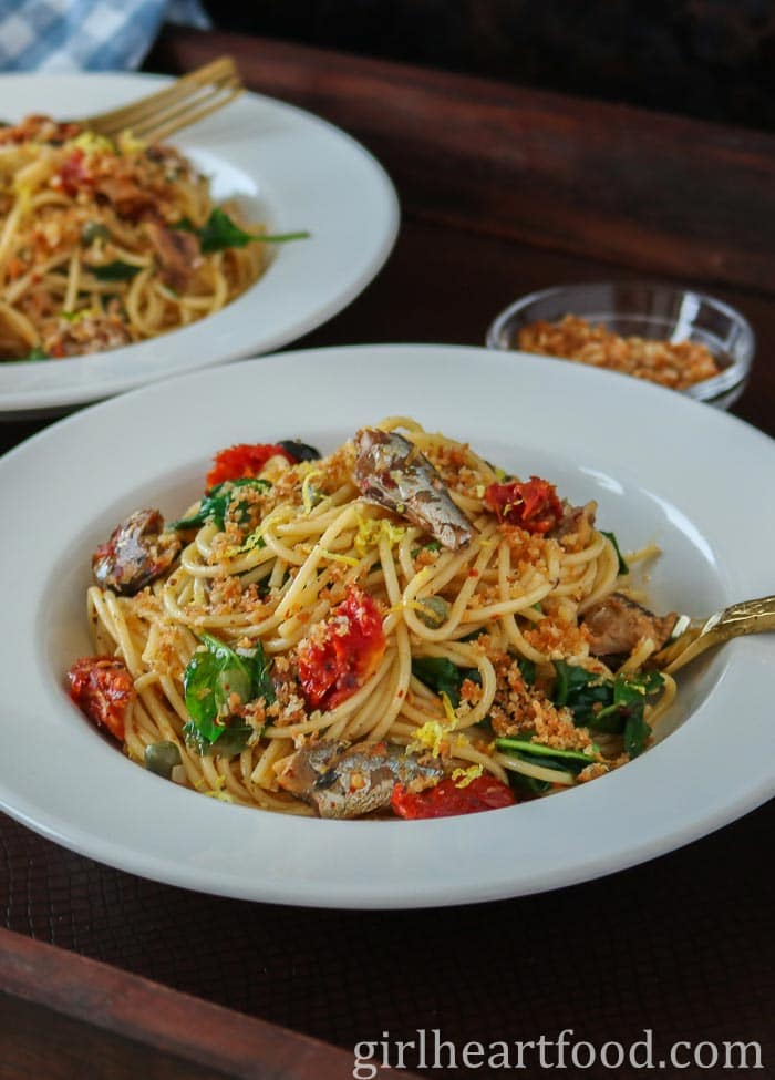 Round white dish of sardine spaghetti with sun-dried tomatoes and spinach with a gold fork stuck into it.