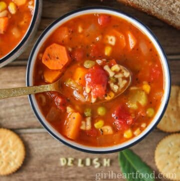 Bowl of homemade vegetable alphabet soup next to some crackers.