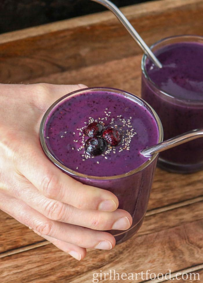 Hand holding a glass of blueberry mango smoothie.