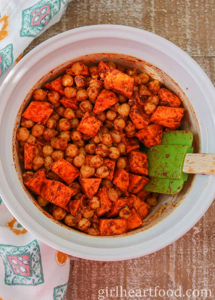 Seasoned chunks of sweet potato and chickpeas in a white bowl, being stirred with a spatula.