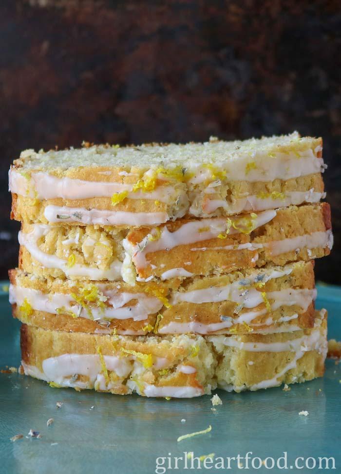Stack of four slices of glazed lemon and lavender loaf.