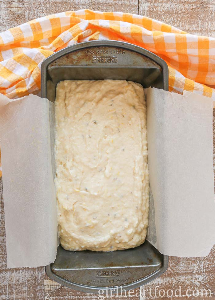 Batter for a loaf cake in a parchment paper lined loaf pan.