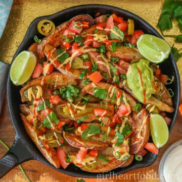 Cast-iron skillet of loaded wedges with three wedges of lime on top.