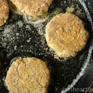 Old-fashioned salmon patties frying in a cast-iron pan.