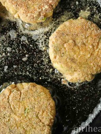 Old fashioned salmon patties frying in a cast iron pan.