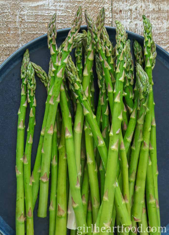 Raw asparagus stalks on a blue plate.