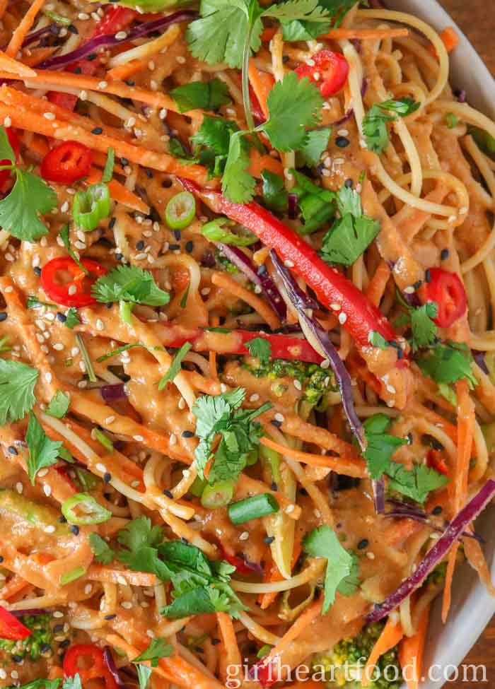 Tight close-up of peanut butter sauce noodles with vegetables.