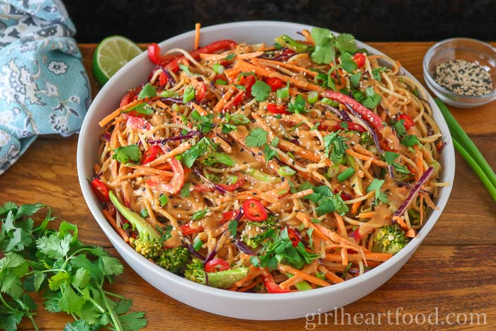 Dish of noodles with peanut sauce and vegetables alongside cilantro, lime, sesame seeds and green onion.