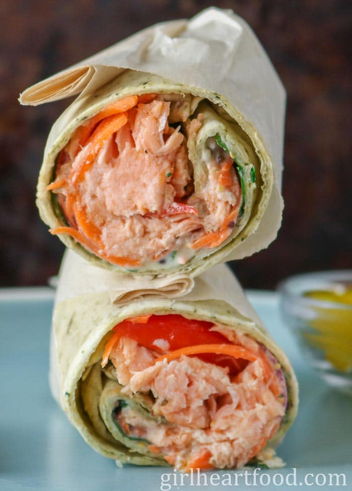 A salmon wrap that has been cut in half with the two halves stacked on top of each other on a blue plate.