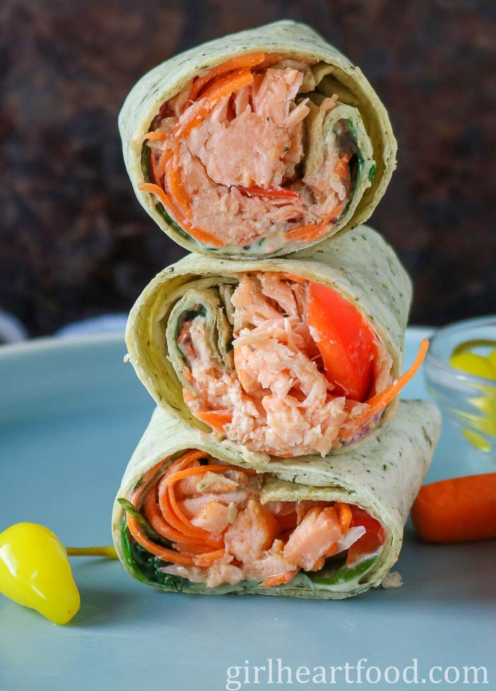 Stack of three fresh salmon and veggie wraps on a blue plate.