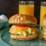 Scrambled egg and cheese sandwiches with tomato and avocado on a blue board next to glasses of orange juice and eggs.
