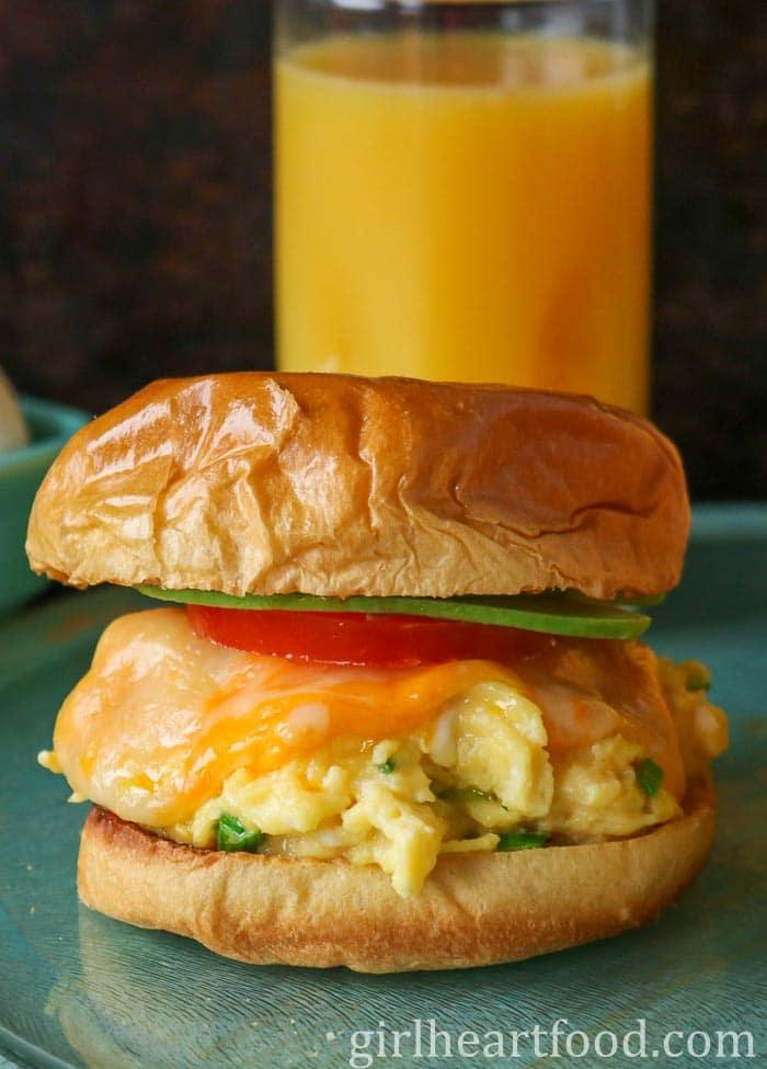 Scrambled egg and cheese sandwich on a brioche bun with tomato and avocado.