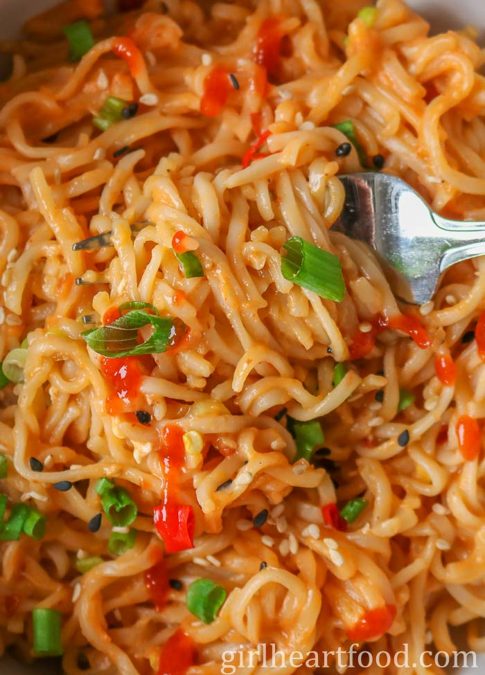 A close up of a fork scooping up  ramen noodles with a sriracha, green onion and sesame seeds on top.