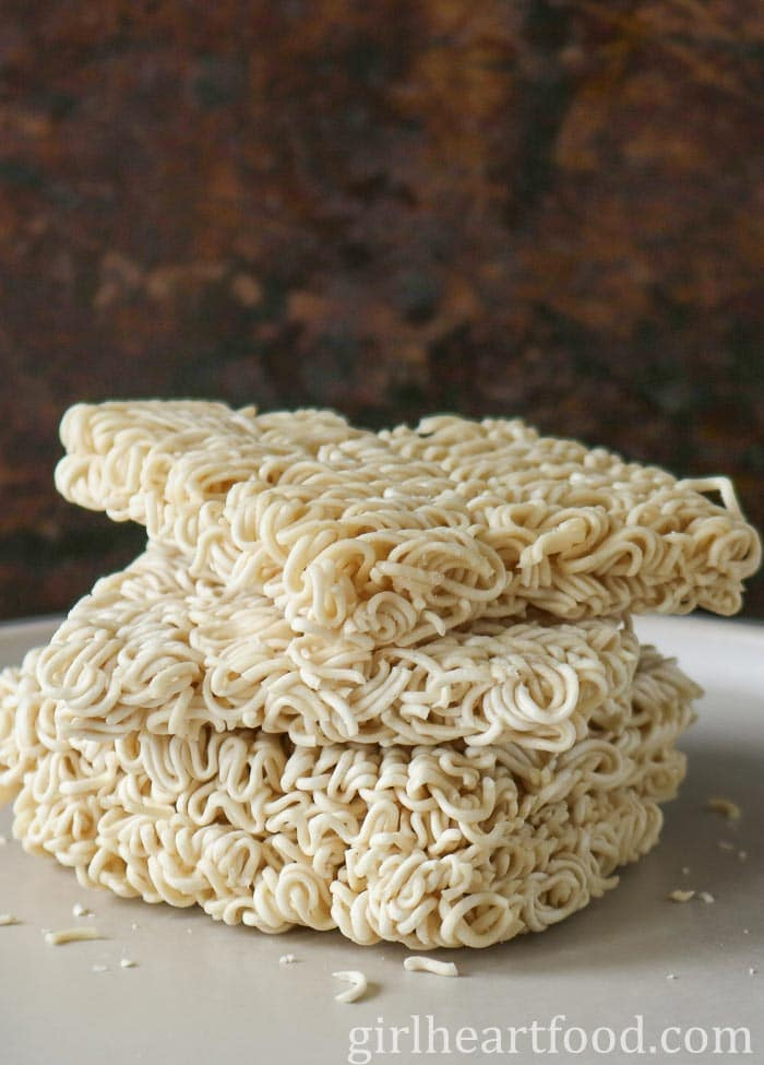 Stack of uncooked ramen noodles on a plate.