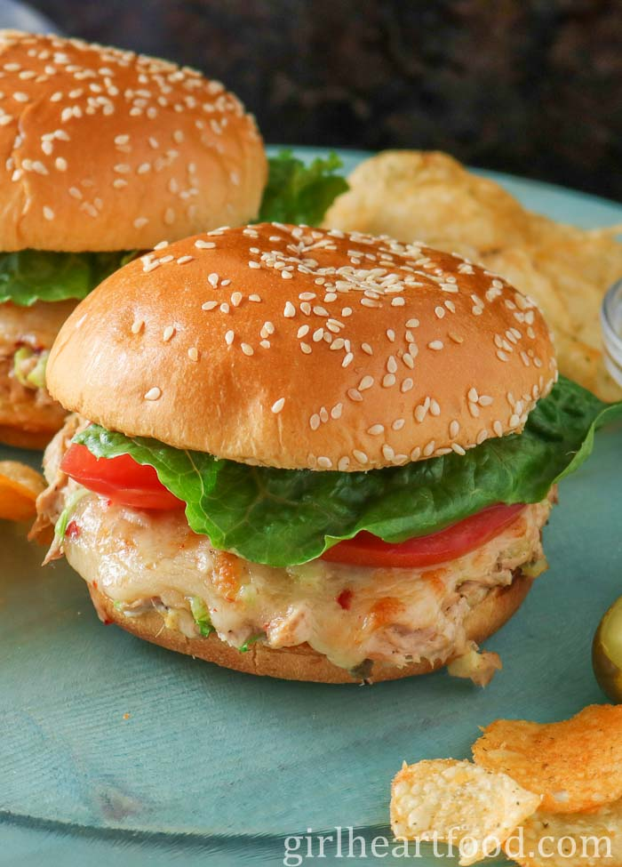 Tuna melt sandwiches with tomato and lettuce next to some potato chips.