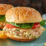 Tuna melt on a hamburger bun with tomato and lettuce.