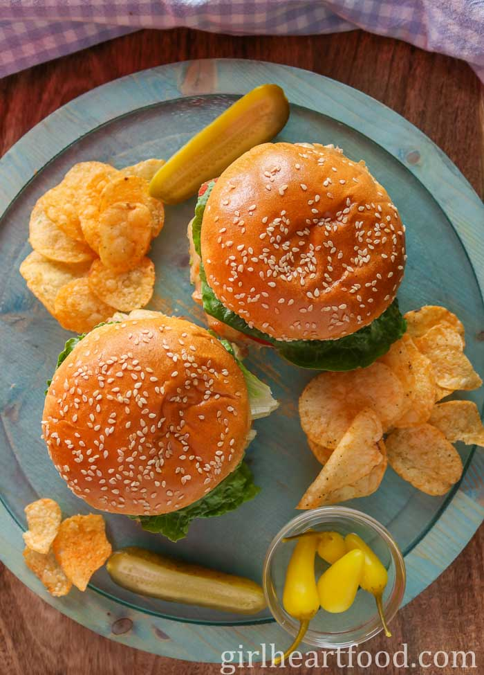 Overhead shot of two sandwiches on a blue board next to pickle, peppers and potato chips.