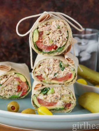 Tuna salad wraps on a blue plate next to pickle, hot pepper and olives.