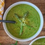 Bowl of asparagus spinach soup garnished with asparagus and lemon zest and drizzled with oil.