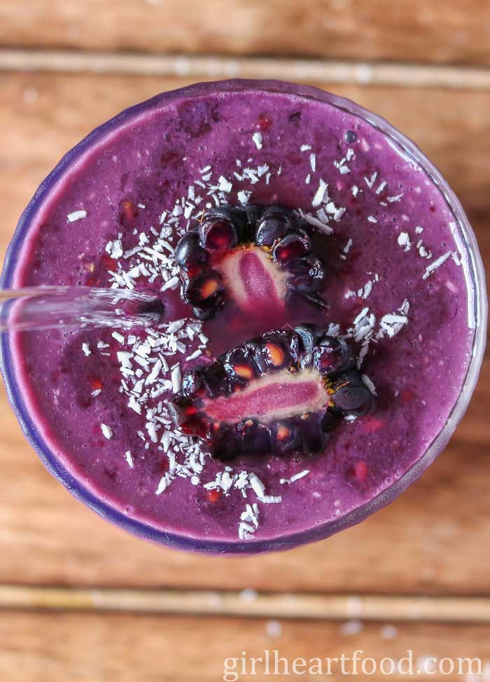 Close-up overhead shot of a blackberry coconut smoothie with a cut blackberry and coconut over top.
