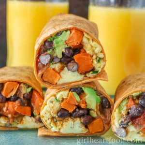 Stack of two vegetarian breakfast wraps with glasses of juice behind them.