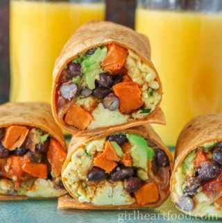 Vegetarian breakfast wraps with glasses of juice behind them.