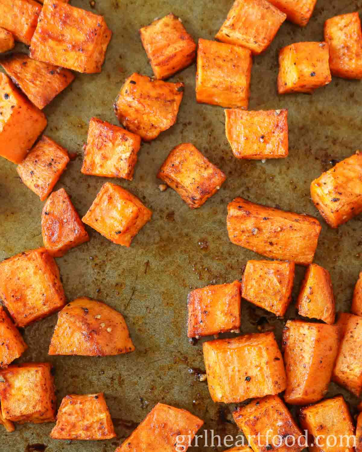 Cubes of roasted sweet potato on a sheet pan.