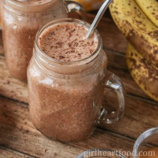 Large mug of chocolate peanut butter banana smoothie next to bananas.