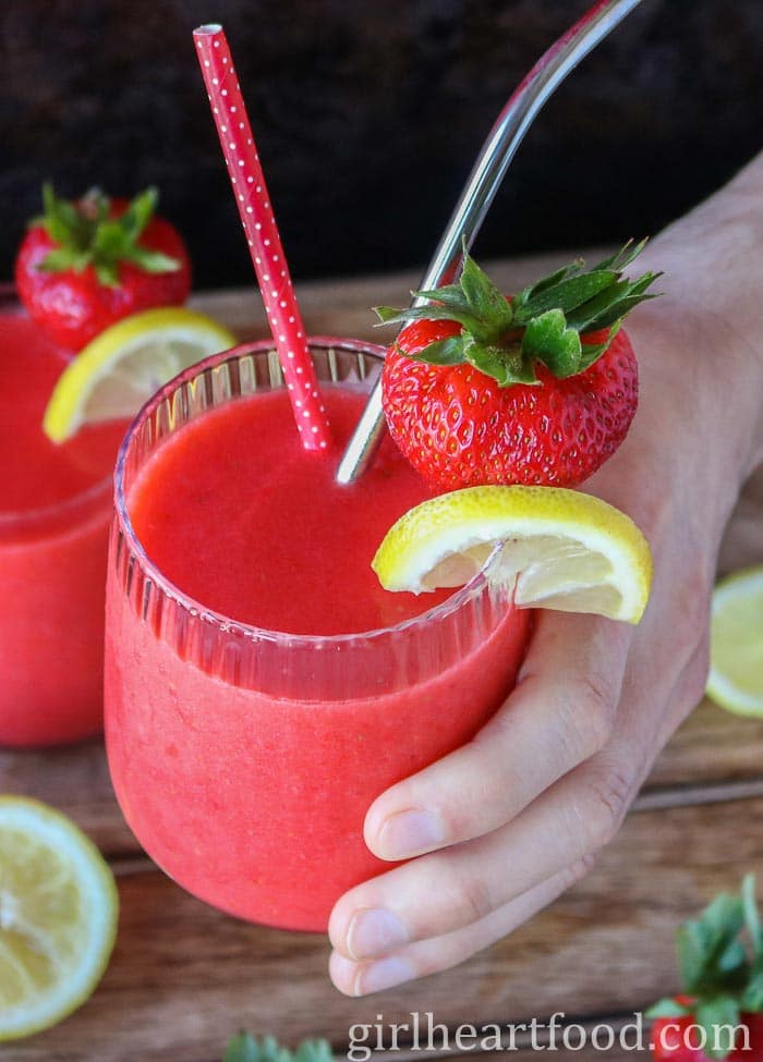 Someone holding up a glass of frozen fruit drink made with strawberries and lemon and garnished with a strawberry and lemon slice.