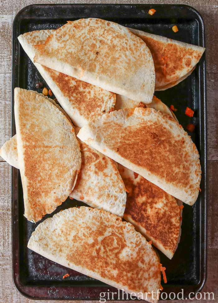Crispy quesadillas piled on a baking tray.