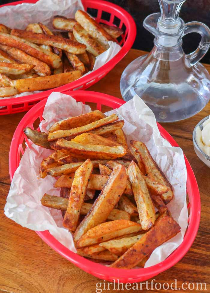 Two baskets with crispy oven fries next to a bottle of vinegar.