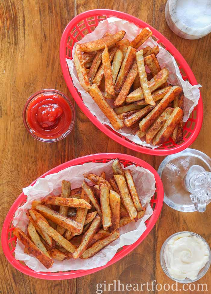 Two baskets of baked French fries next to dishes of salt, ketchup, mayo and bottle of vinegar.