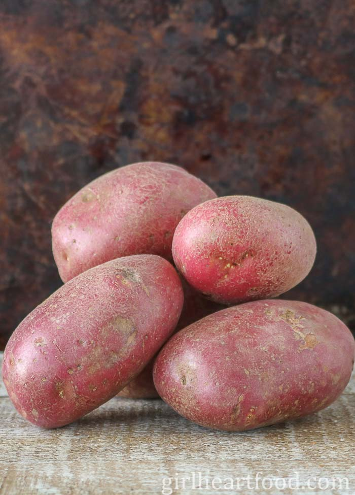 A stack of uncooked and unpeeled red potatoes on a wooden board.