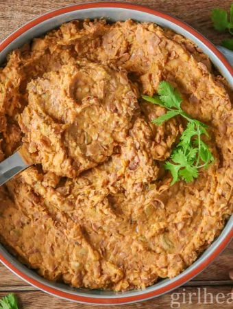 Large round dish of homemade refried beans garnished with fresh cilantro with a large spoon scooping some up.