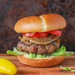 Ground moose burger with caramelized onions, lettuce and tomato on a bun.